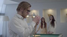 Handsome bearded man in glasses and shirt rubbing a billiard cue with chalk in front of two blurred figures of young. Handsome blond bearded man in glasses and stock video footage