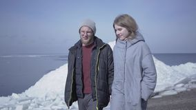 Handsome blond bearded man walking with pretty woman holding hands. Amazing view of a snowy North or South Pole on the. Handsome blond bearded man walking with a stock footage