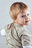 Handsome  blond boy  stands in half-turn. Positive human emotion facial expression feelings Royalty Free Stock Photo