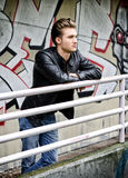 Handsome blond haired young man on metal railing Royalty Free Stock Images