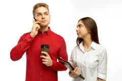 A handsome blond man puzzled listens to the boss on the phone. Dissatisfied with the Secretary waiting for instructions. royalty free stock photos