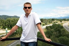 Handsome blond man on scenic highway background Royalty Free Stock Image
