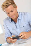 Handsome blond man sending short message on smartphone Stock Photos