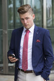 Handsome blond man in suit standing outside with his phone Royalty Free Stock Photography