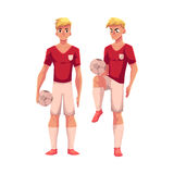 Handsome blond soccer player in uniform standing with football ball Royalty Free Stock Photos