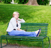 Handsome blond woman sitting on bench at garden Stock Photos