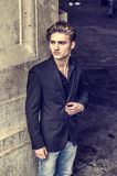 Attractive blue eyed, blond young man leaning against white wall Royalty Free Stock Photography