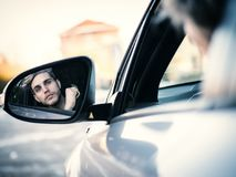 Handsome Young Man Driving a Car. Handsome Blond Young Man Driving a Car, Seen in the Rear Mirror Royalty Free Stock Photos