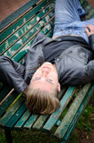 Handsome blond young man laying on park bench Stock Image