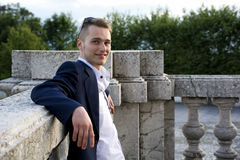 Handsome blond young man on marble banister Royalty Free Stock Photo