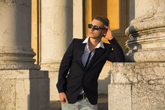 Handsome blond young man with marble columns behind him Royalty Free Stock Photos