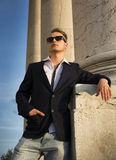 Handsome blond young man with marble columns behind him Stock Image