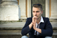 Handsome blond young man with marble columns behind him Royalty Free Stock Images