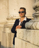 Handsome blond young man among marble columns Stock Photo