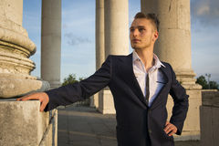 Handsome blond young man among marble columns Royalty Free Stock Images
