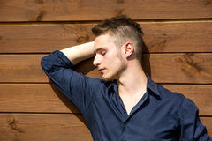 Handsome blond young man outside against wood wall Stock Photography