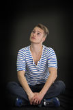 Handsome blond young man sitting on black background Stock Photo