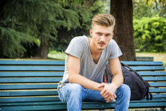 Handsome blond young man sitting on park bench Royalty Free Stock Photos