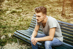 Handsome blond young man sitting on park bench Royalty Free Stock Images