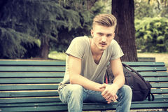 Handsome blond young man sitting on park bench Stock Image