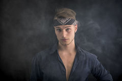 Handsome blond young man wearing bandana, smoke around him. Dark background Stock Images