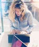 Handsome blonde businesswoman working at the modern office loft.Coworker using electronic touch tablet computer on sunny. Workplace.Vertical. Blurred background stock photos