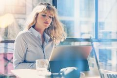 Handsome blonde businesswoman working at the modern office loft.Coworker using electronic touch tablet computer on sunny. Workplace.Horizontal. Blurred stock images