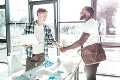Handsome blonde man shaking hands with his visitor. Nice to meet you. Delighted dark-skinned male person standing in semi position and stretching hand while stock photo