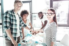 Handsome blonde man standing near his colleagues. Express positivity. Delighted young people keeping smiles on faces and holding hands together while looking at royalty free stock image