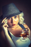 Handsome blonde woman in hat drinking cognac, business style Royalty Free Stock Photos