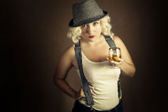Handsome blonde woman in hat drinking cognac, business style Stock Photography