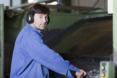 Handsome blue collar worker in factory. Blue collar worker at machine in factory stock photos