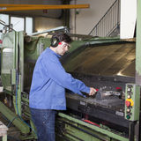 Handsome blue collar worker in factory. Blue collar worker at machine in factory stock image