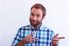 A handsome blue-eyed man with a beard directs you with the movement of hands. Nice blue-eyed man with beard pointing at something Stock Image
