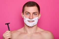 Handsome blue eyed young man with dark hair, shaving gel, holds sharp razor, has muscular body, looks directly at camera, shaves. Beard, isolated over pink stock photo