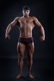 Handsome bodybuilder demonstrates his powerful body. Handsome man with perfect powerful body demonstrates his strong muscles Royalty Free Stock Photo
