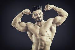 Handsome bodybuilder doing biceps pose Stock Photos