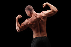Handsome bodybuilder flexing his back muscles Stock Photos