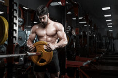 Handsome bodybuilder guy prepare to do exercises with barbell Stock Images