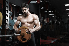 Handsome bodybuilder guy prepare to do exercises with barbell stock photo