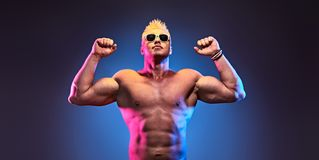 Handsome bodybuilder man naked male muscular torso. Charismatic Muscular man with naked torso jump in colorful neon light. Sexy bodybuilder fitness guy Having stock image