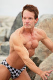 Handsome bodybuilder on the rocks Stock Photo