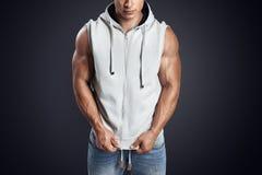 Handsome bodybuilder wearing gray sleeveless hoodie. Close up photo of attractive fitness man wearing blank light gray sleeveless hoodie. Studio shot on dark Stock Photo