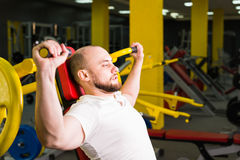 Handsome bodybuilder works out excercise in gym Stock Image