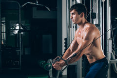 Handsome bodybuilder works out pushing up excercise in gym Royalty Free Stock Photos
