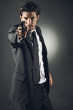 Handsome bodyguard aiming. Handsome bodyguard with elegant dress aiming . Dark toning stock photos