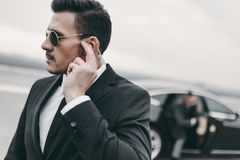handsome bodyguard of businessman listening message stock photography