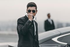 Handsome bodyguard in sunglasses talking. By portable radio stock image