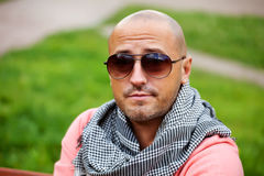 Handsome bold man wearing neck handkerchief resting Royalty Free Stock Images