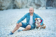 Handsome bold stylish dressed in jeans man in blue cap sitting on a beach sea side together with pretty english bulldog. stock photo